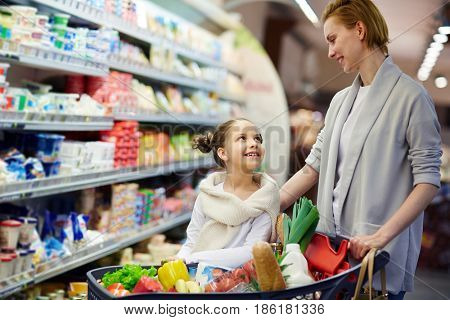 Portrait of happy woman shopping in grocery store with little girl, smiling and looking at each other caringly while pushing cart full of food