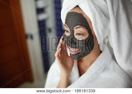Portrait of beautiful Asian woman applying face mask, looking in mirror and smiling