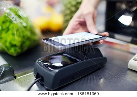 Closeup shot of female hand holding smartphone over terminal using NFC payment technology in grocery store