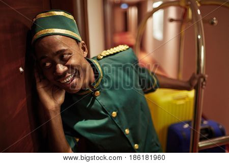 Portrait of young African boy working as bellhop in luxury hotel, listening at the room door delivering luggage