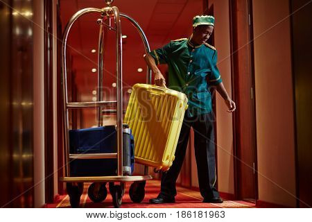 Portrait of African bellboy with luggage cart in hotel hallway, bringing bags to guest rooms