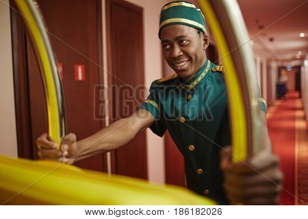 Portrait of smiling young bellhop of African ethnicity working in hotel, pushing luggage cart delivering bags to hotel rooms in hallway
