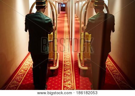 Back view portrait with mirror reflection of bellboy pushing luggage cart in hotel hallway, delivering bags to rooms
