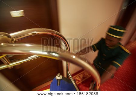 High angle portrait of bellboy pushing luggage cart in hotel hallway, fast blurred motion