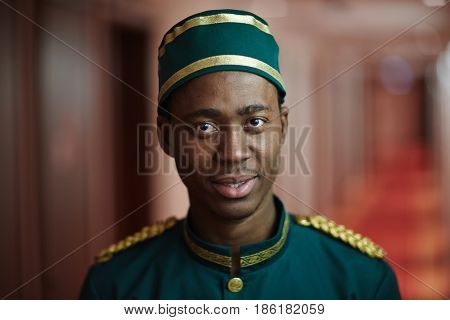 Portrait of smiling young bellhop of African ethnicity working in hotel, welcoming tourists looking at camera