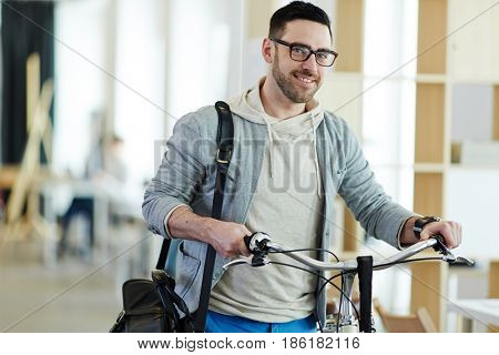 Modern businessman with bicycle leaving office by end of working day