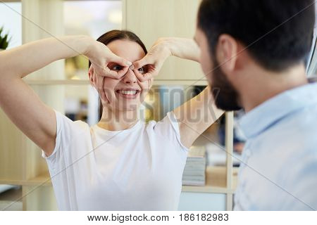 Smiley young woman making silly face while looking at co-worker