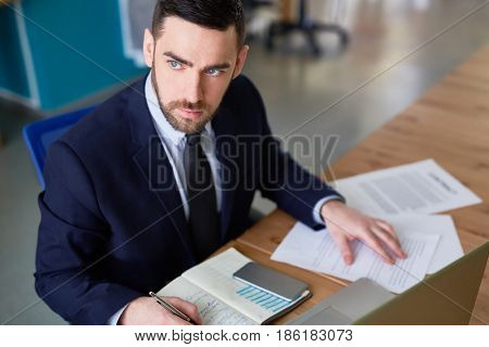 Concentrated economist thinking of data while planning work
