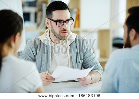 Confident man answering questions of employers during interview