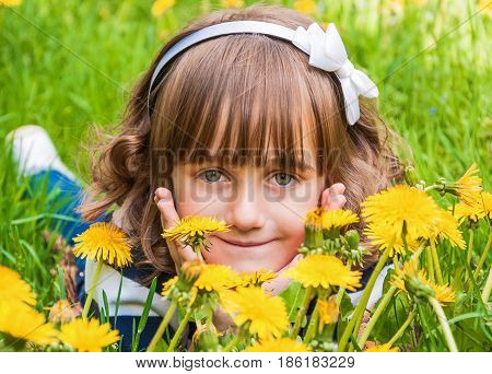 Portrait of cute little smiling girl with big gray eyes among dandelions