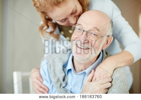 Smiley man with grey stubble looking at camera while his wife embracing him