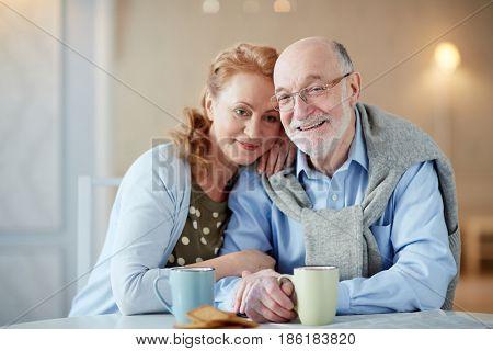 Happy senior spouses having tea by table