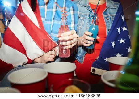 Mid-section portrait of two teenage girls drinking cocktails at late night party, wrapped in American banner