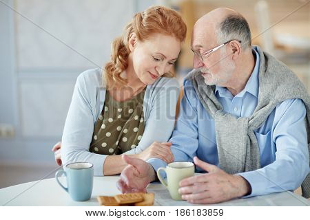 Serene female listening to her spouse by tea