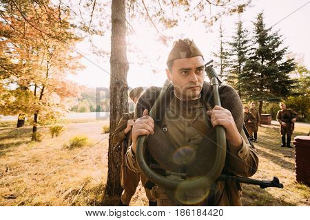 Dyatlovichi, Belarus - October 1, 2016: Reenactor Man Dressed As Russian Soviet Red Army Infantry Soldier Of World War II Preparing For Marching In Forest With Machine-gun At Historical Reenactment