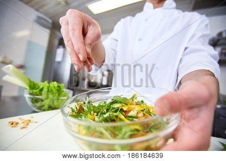 Chef seasoning salad by ground nutmeg