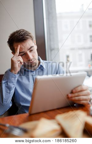Portrait of tired business man sulking at table in cafe looking at tablet screen