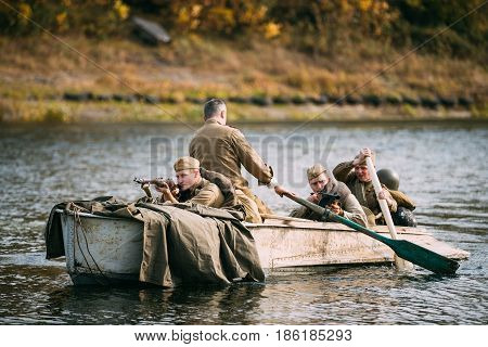 Dyatlovichi, Belarus - October 1, 2016: Group Of Men Reenactors Dressed As Russian Soviet Red Army Infantry Soldiers Of World War II Make Crossing Of River On A Boat