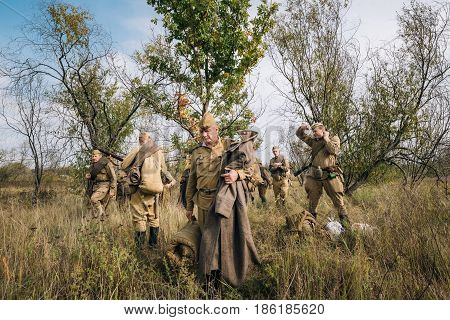 Dyatlovichi, Belarus - October 1, 2016: Group Of Reenactors Dressed As Russian Soviet Red Army Soldiers Of World War II Preparing For Marching In Forest At Historical Reenactment