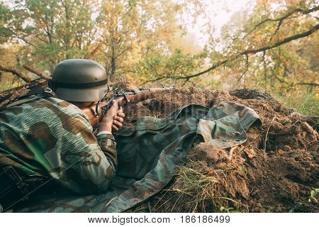 Unidentified Re-enactor Dressed As German Wehrmacht Infantry Soldier In World War II Hidden Sitting With Rifle Weapon In An Ambush In Trench In Autumn Forest At Sunset Or Sunrise