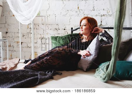 Redhead woman in black lace peignoir on the bed in her bedroom among velvet pillows resting. Sensual boudoir portrait.