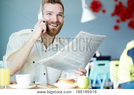 Calling businessman with newspaper having lunch break