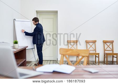 Smart businessman drawing financial graph or chart on whiteboard