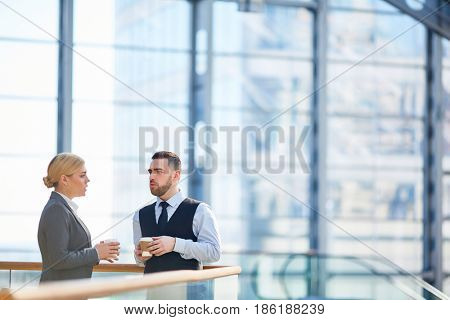 Portrait of two successful business people, man and woman, talking during break in gass hall of modern building, both holding coffee cups