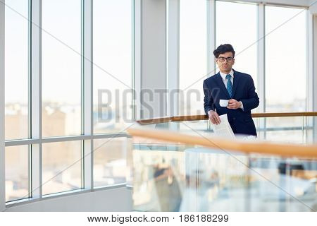 Serious employer with cup of coffee and newspaper