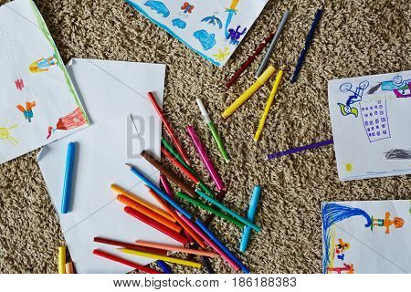 Set of crayons and highlighters, pictures of kids and empty papers on the floor