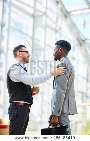 Portrait of smiling businessman chatting with African-American partner patting him on shoulder in modern glass hall of office building