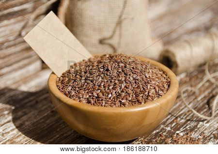 Close up of brown flax seeds in wooden bowl on a rustic table. Superfood: linseeds are high in omega-3 fatty acids essential for good health. Healthy eating vegan diet concept.
