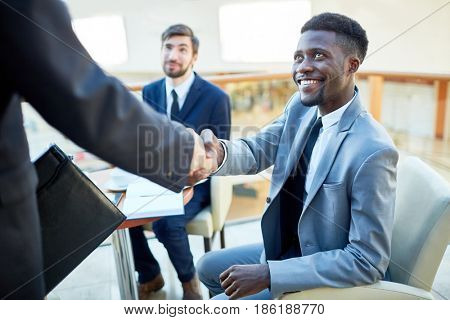 Portrait of smiling young African-American  businessman shaking hands with partner, sitting at table in meeting