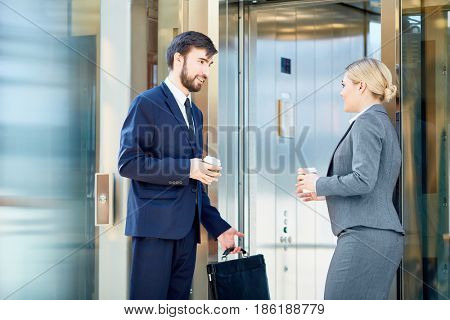 Portrait of two business colleagues dressed in formalwear meeting and talking by elevator on way to work, both holding coffee cups