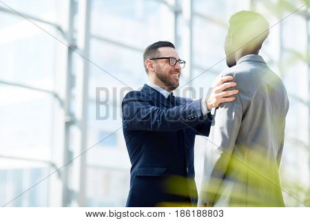 Portrait of smiling businesman patting on shoulder Afro-American partner standing in modern glass hall of office building