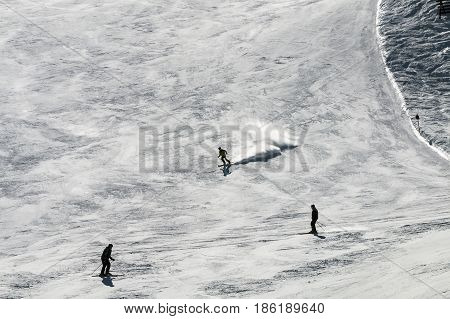 Skiers on the black run of the Gaislachkogel in Austria against the sunlight.