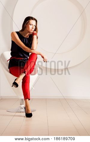Beautiful brunette on red chair