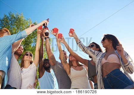 Company of buddies raising hands with drinks while toasting