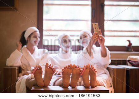 group of famale friends in spa have fun, celebrate bachelorette party with face mask