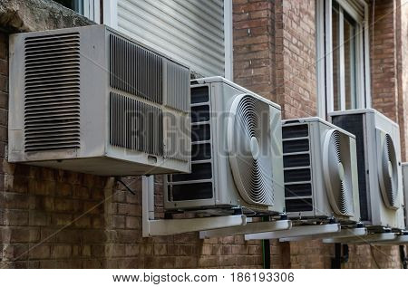 Air conditioner systems in the wall of a building. Air conditioning is based in removing heat from a confined space to achieve a more comfortable interior environment