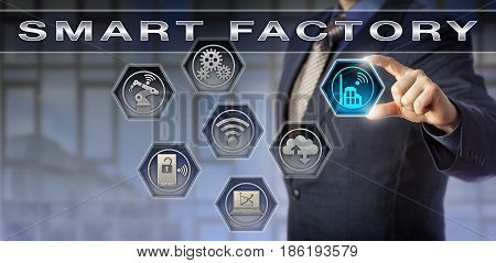 Male blue chip plant manager activating a Smart Factory application. Technology concept for digital manufacturing cyber physical systems industry 4.0 and data exchange via internet of things.