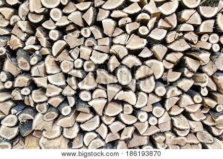 Background of dry chopped oak firewood logs stacked up on top of each other in a pile. Background or a texture