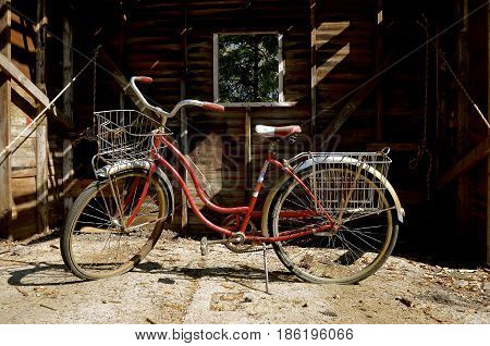 A vintage bike is parked in front of a an old shed which is being demolished,