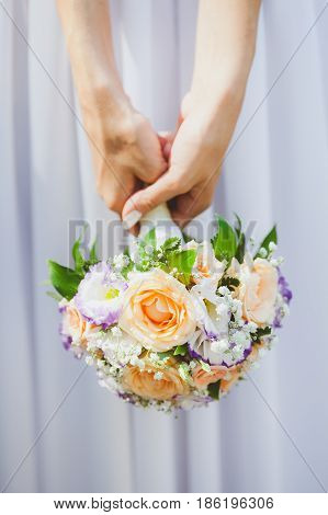 Bride in a white dress holding bouquet from spring flowers in hands on a white background close up. marriage, love, bride, wedding - concept. gatherings of bride.