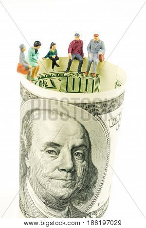 miniature figurines sitting on the edge of 100 dollar banknote on white background