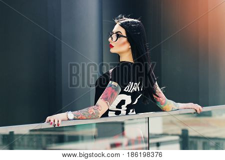 Tattoed Fashion. Portrait Of Attractive Tattoed Hipster Girl Posing To Camera Against Urban Backgrou