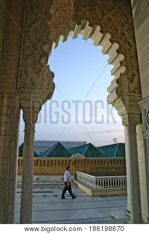 RABAT MOROCCO - MAY 17 2006: A man walks past an Islamic-style arch of the Mausoleum of Mohammed V on the Yacoub al-Mansour esplanade at dusk in Rabat the capital city of Morocco.