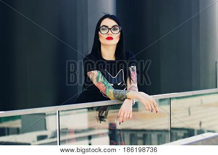Tattoo Fashion. Portrait Of Fashionable Tattoed Hipster Girl With Red Lips Posing Against Urban Back