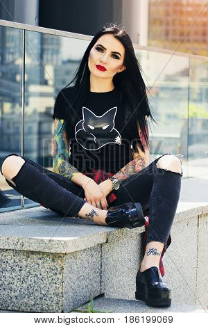 Gorgeous Tattoed Woman. Portrait Of Young Tattoed Hipster Girl Posing Against Urban Background.
