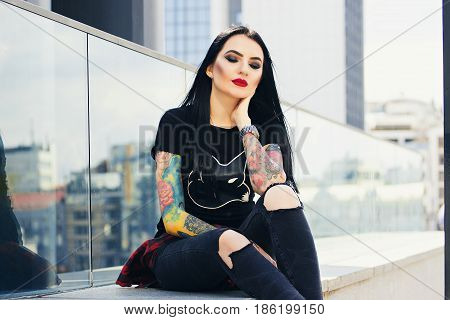 Gothic Beauty. Portrait Of Attractive Tattoed Hipster Girl With Red Lips Posing To Camera While Sitt